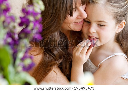 Close up portrait detail of an attractive mother and her young daughter hugging and being close at home with girl eating a fresh natural grape. Loving portrait of family holidays, outdoor lifestyle. - stock photo