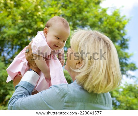 Close up portrait grandmother lifting grandchild up and playing - stock photo