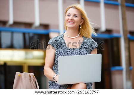 Close Up portrait, Happy and Smiling old senior business woman 60-65 years, using a laptop computer in New York city park, looking to up - stock photo