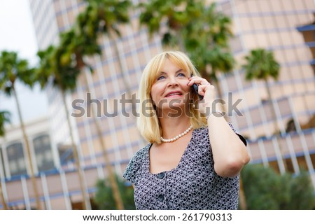 Close Up portrait happy smiling old business woman 60 years in the downtown talking with mobile phone, Lifestyle woman on phone, Business concept - business woman calling on the phone in street - stock photo