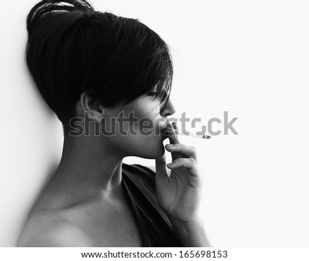 Close-up portrait in profile of a girl with a cigarette and a cool hairstyle , black and white - stock photo