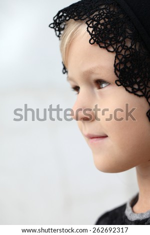 Close-up portrait in profile of adorable smiling child girl. Girl on a religious holiday with his head covered. A child with a kerchief on her head. - stock photo