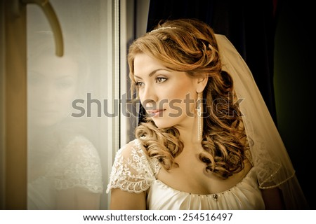 close up portrait in warm tone of a attractive woman  in a bridal dress and veil - stock photo