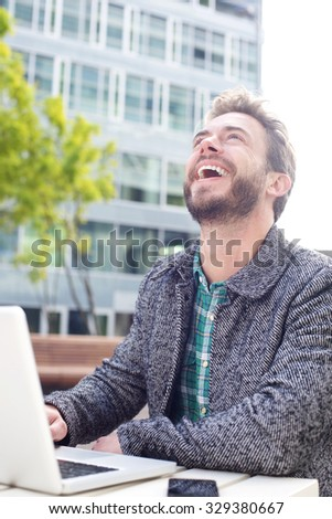 Close up portrait man laughing with laptop outdoors - stock photo
