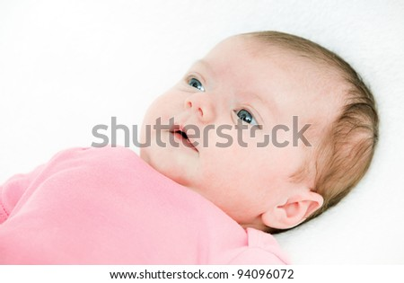 Close up portrait newborn baby lying in bed - stock photo