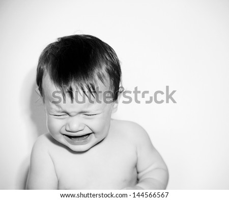 Close up portrait of a baby boy with being unhappy and crying against a white background with a retro style. - stock photo