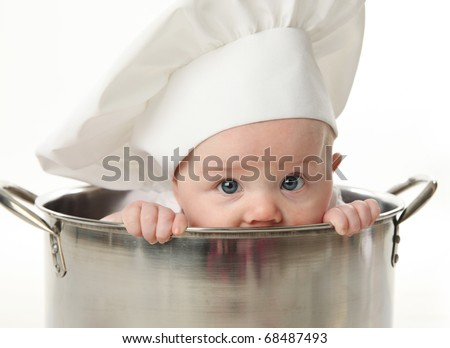 Close up portrait of a baby sitting wearing a chef hat sitting inside a large cooking stock pot, isolated on white - stock photo
