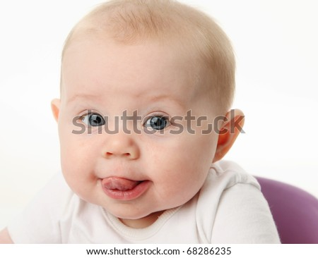 Close up portrait of a baby with tongue sticking out - stock photo