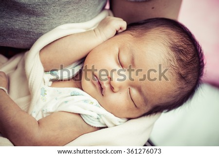 close-up portrait of a beautiful Asian sleeping newborn baby after 14 day birth in mother's arms. - stock photo