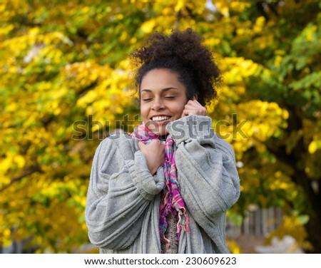 Close up portrait of a beautiful black woman enjoying autumn - stock photo