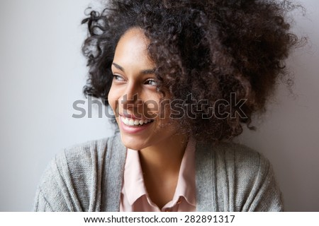 Close up portrait of a beautiful black woman smiling and looking away - stock photo