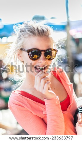 close-up portrait of a beautiful blond young woman with sunglasses, eating an olive on a market on a sunny day - stock photo