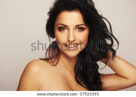 Close-up portrait of a beautiful brunette model in studio on light background - stock photo
