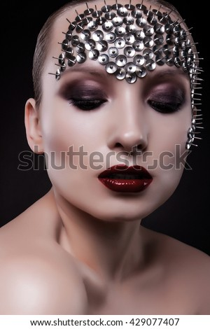 close-up portrait of a beautiful girl with bright makeup and spikes on his face on a black background. Red lips. metal spikes. beautiful eyes. - stock photo