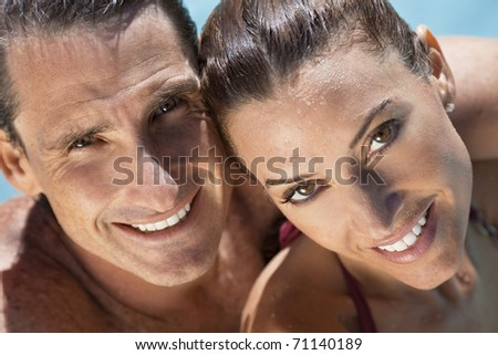 Close up portrait of a beautiful happy man and woman couple in a sun bathed swimming pool smiling with perfect teeth. - stock photo