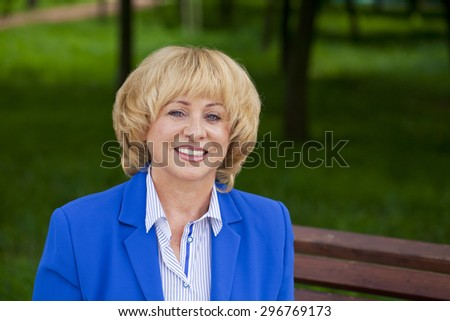 Close up portrait of a beautiful middle aged woman in a blue business suit - stock photo
