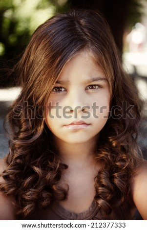 Close-up portrait of a beautiful moody little girl - stock photo