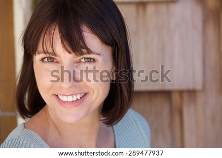 Close up portrait of a beautiful older woman smiling - stock photo