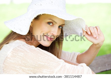 Close up portrait of a beautiful older woman smiling with hat - stock photo