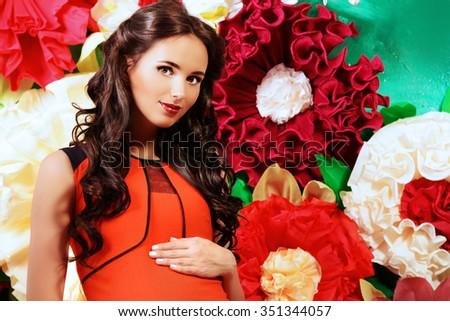 Close-up portrait of a beautiful pregnant woman posing over big bright flowers. Clothes for pregnant women. Beauty, fashion. - stock photo