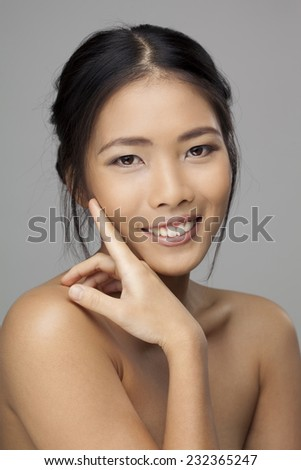 Close-up portrait of a beautiful smiling brunette holding hand by face and looking at camera. - stock photo