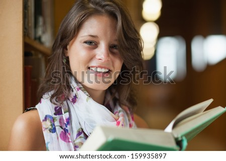 Close-up portrait of a beautiful smiling female holding a book against blurred background - stock photo
