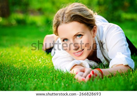 Close-up portrait of a beautiful smiling woman lying on a grass outdoor. She is absolutely happy.  - stock photo