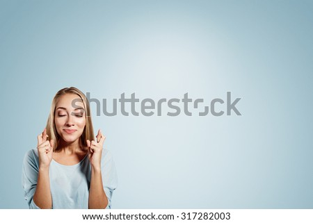 Close-up portrait of a beautiful woman closing her eyes, crossing her fingers hoping for the best,isolated on blue background - stock photo