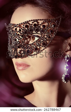 Close-up portrait of a beautiful woman in venetian mask. Carnival, masquerade. Jewellery, gems. - stock photo