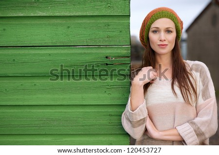 Close up portrait of a beautiful woman leaning against a green wooden wall outdoors. Possibility for copy space - stock photo