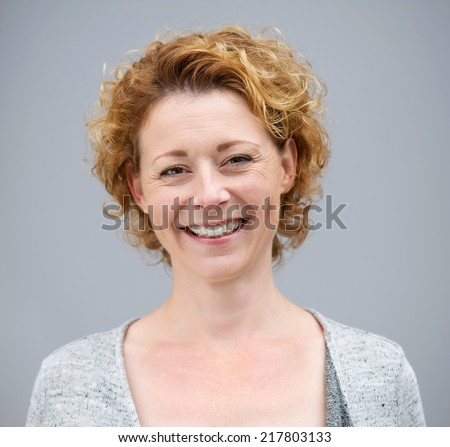 Close up portrait of a beautiful woman smiling on gray background - stock photo