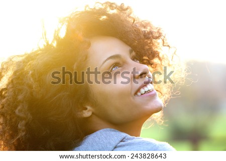 Close up portrait of a beautiful young african american woman smiling and looking up - stock photo