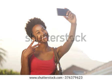 Close up portrait of a beautiful young african woman gesturing peace sign while taking a selfie - stock photo