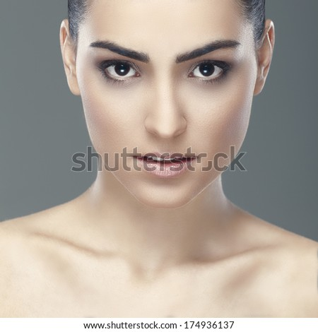 Close-up portrait of a beautiful young black eyed woman holding hands by her face and looking to the side.  - stock photo