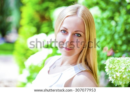 Close up portrait of a beautiful young blonde woman, outdoors - stock photo