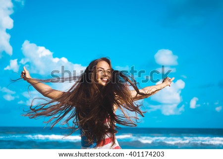 close-up portrait of a beautiful young brunette girl with long hair on a background of blue sea with waves and sky with clouds on a sunny day, lifestyle, posing and smiling, wind - stock photo