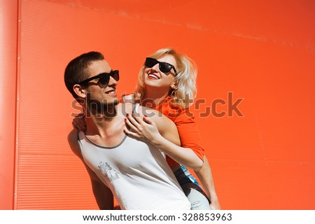 close-up portrait of a beautiful young couple in love bright blonde girl with red lips and a guy with a beard wearing a cap hipsters on a yellow background smiling and posing lifestyle  white shirt - stock photo