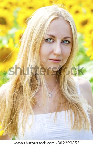 Close up portrait of a beautiful young girl in a white dress on a background field of sunflowers - stock photo