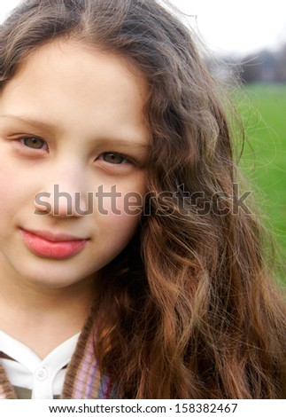 Close up portrait of a beautiful young girl with a gentle smiling expression, wearing a stripy knitted jumper while in a green grass park field during a winter autumn day outdoors. - stock photo