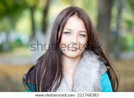 close-up portrait of a beautiful young girl with blue eyes in  park - stock photo