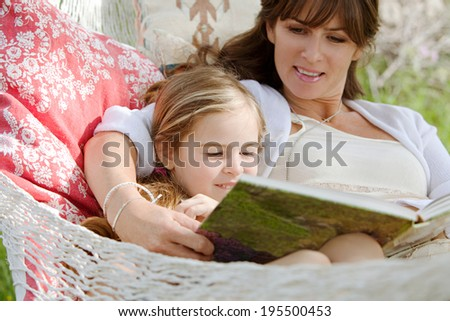 Close up portrait of a beautiful young mother and her young daughter laying down in a hammock relaxing together, reading a children stories book during a sunny summer day. Family lifestyle outdoors. - stock photo