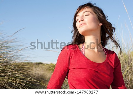 Close up portrait of a beautiful young woman breathing fresh air while sitting on a beach sand dunes with her eyes closed, leaning her head back and enjoying the breeze on vacation. - stock photo