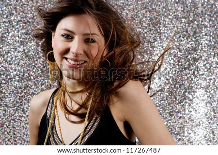 Close up portrait of a beautiful young woman dancing at a party against a silver glitter background. - stock photo