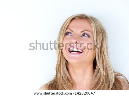 Close up portrait of a beautiful young woman laughing and looking up on white background - stock photo