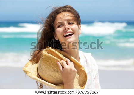 Close up portrait of a beautiful young woman laughing at the beach - stock photo