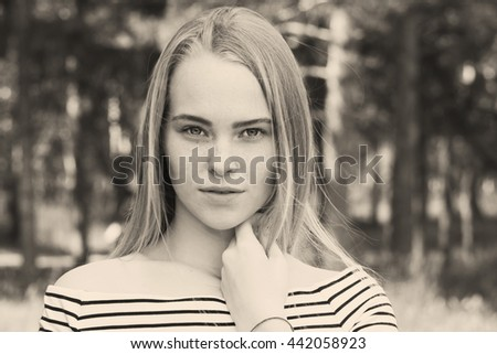 Close-up portrait of a beautiful young woman looking into the camera. A woman in a striped dress on a background of blurred trees. Toned image in the old style - stock photo