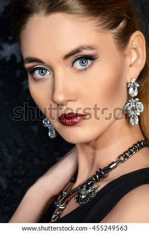 Close-up portrait of a beautiful young woman wearing earrings and necklace with gems. Jewellery. Beauty, fashion. Studio shot.  - stock photo