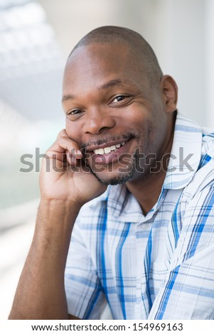 Close-up portrait of a black man smiling and looking at camera - stock photo