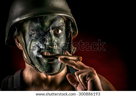 Close-up portrait of a brave soldier in war paint smoking a cigar. Black background. Military, war. Special forces. - stock photo