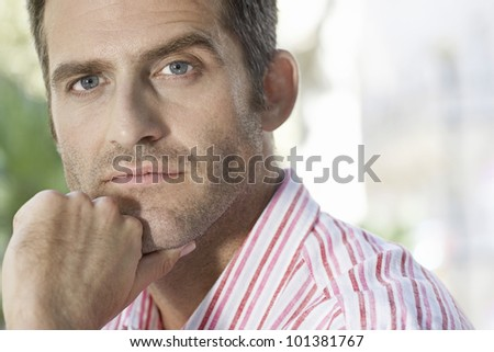 Close up portrait of a businessman looking at camera while outdoors. - stock photo